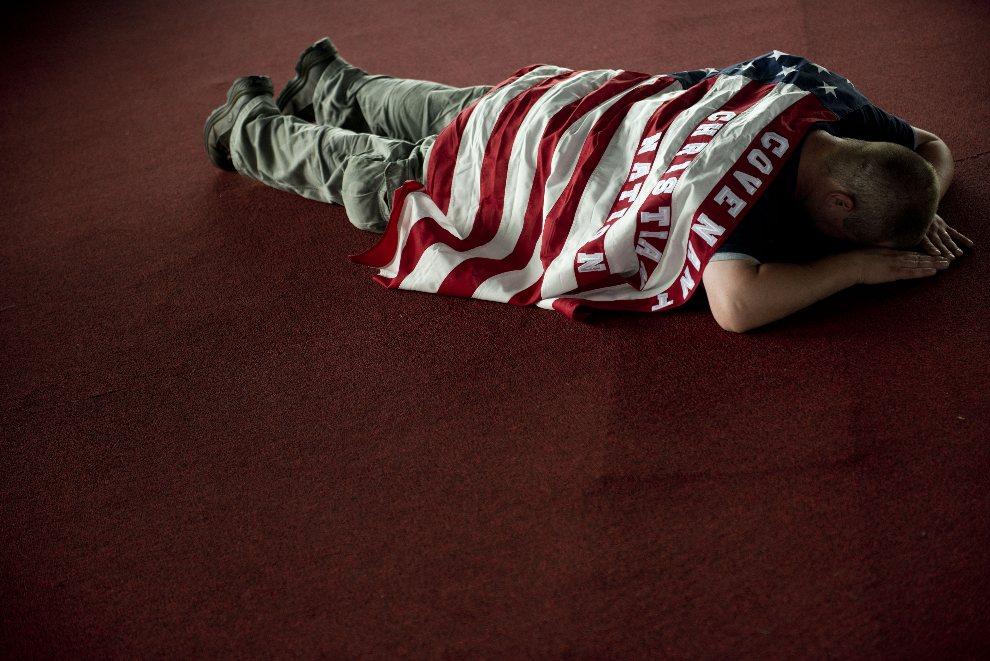 17.USA, Charlotte, 2 września 2012: Nathan Conley okryty flagą modli się w trakcie trwającej konwencji Partii demokratycznej. AFP PHOTO/Brendan SMIALOWSKI