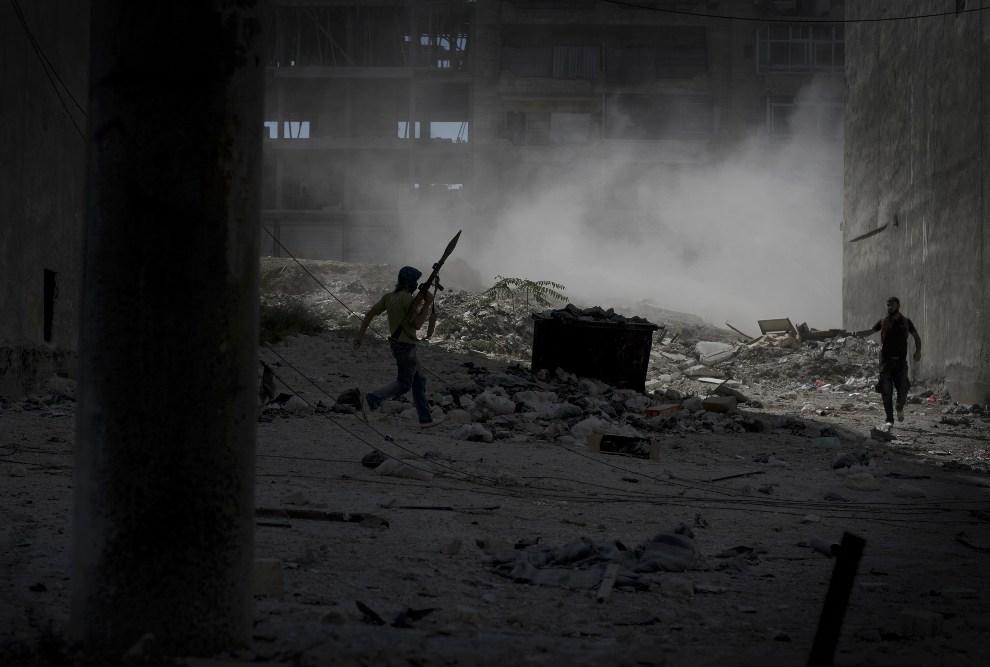 18.SYRIA, Aleppo, 26 września 2012: Rebeliant z RPG ucieka spod ostrzału prowadzonego przez rządowe czołgi. AFP PHOTO/ZAC BAILLIE