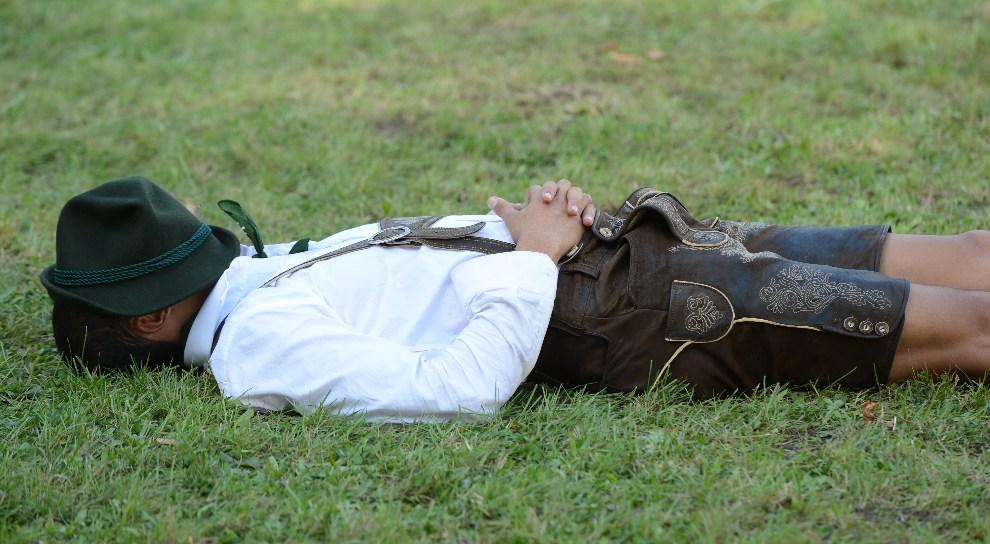 18.NIEMCY, Monachium, 23 września 2012: Uczestnik zabawy odpoczywa na trawniku. AFP PHOTO / CHRISTOF STACHE
