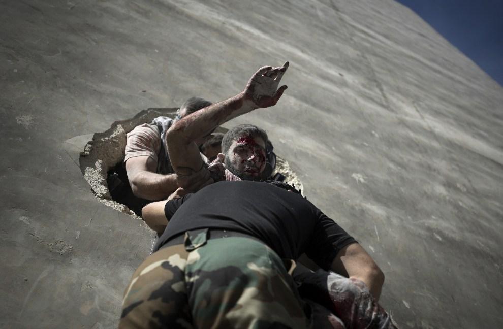 19.SYRIA, Aleppo, 26 września 2012: Ranny rebeliant znoszony przez towarzyszy po drabinie. AFP PHOTO/ZAC BAILLIE