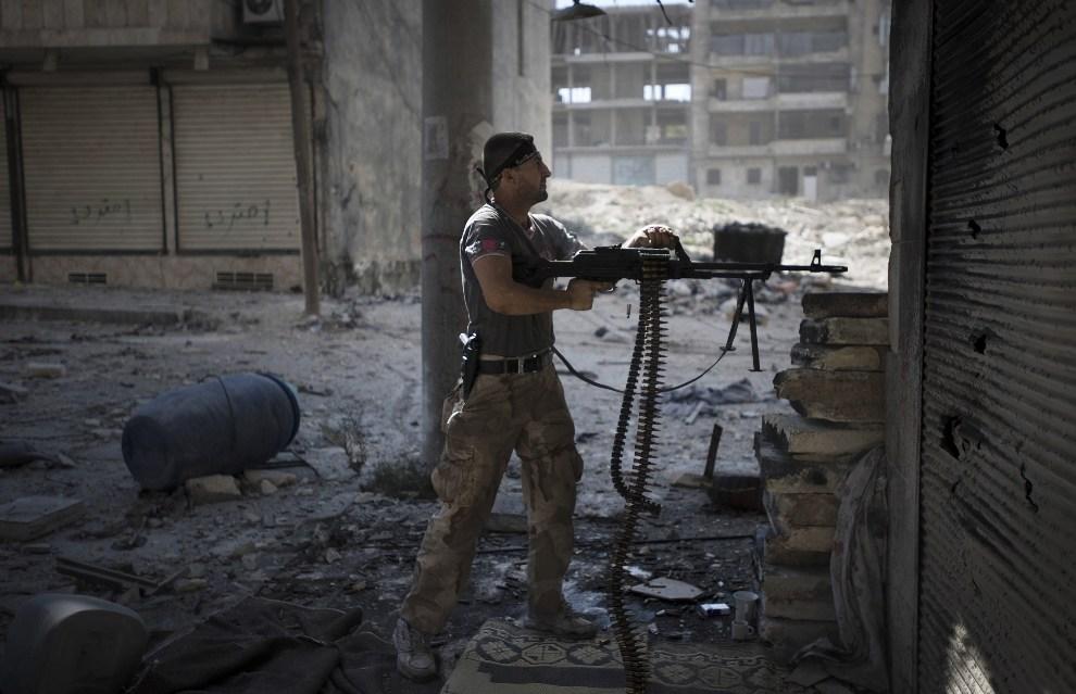 20.SYRIA, Aleppo, 26 września 2012: Rebeliant ostrzeliwuje pozycje wojsk rządowych. AFP PHOTO/ZAC BAILLIE