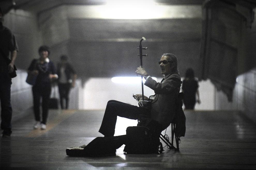 21.CHINY, Pekin, 25 września 2012: Uliczny artysta występujący w przejściu podziemnym. AFP PHOTO/WANG ZHAO