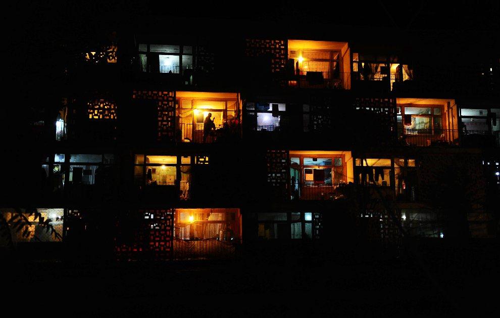 24.AFGANISTAN, Mazar-i-Sharif, 4 wrzesnia 2012: Mężczyzna pali papierosa na balkonie mieszkania w bloku. AFP PHOTO/ Qais Usyan