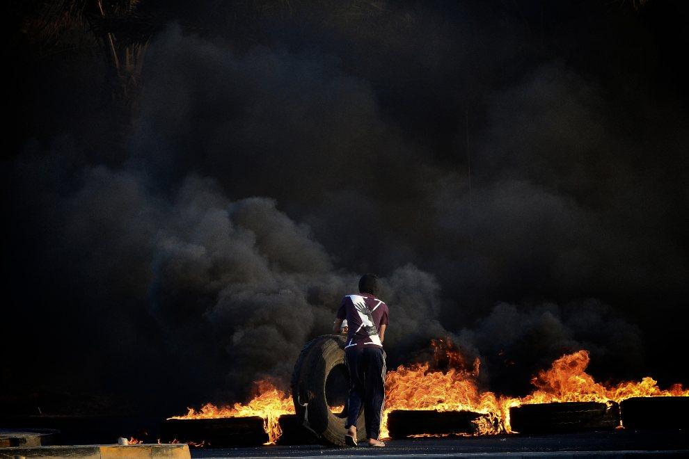 25.BAHRAJN, Sitra, 3 września 2012: Mężczyzna podpala opony podczas starć z policją. AFP PHOTO/MOHAMMED AL-SHAIKH
