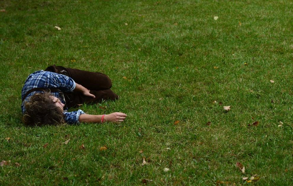 26.NIEMCY, Monachium, 22 września 2012: Uczestnik zabawy odpoczywa na trawniku. AFP PHOTO / CHRISTOF STACHE