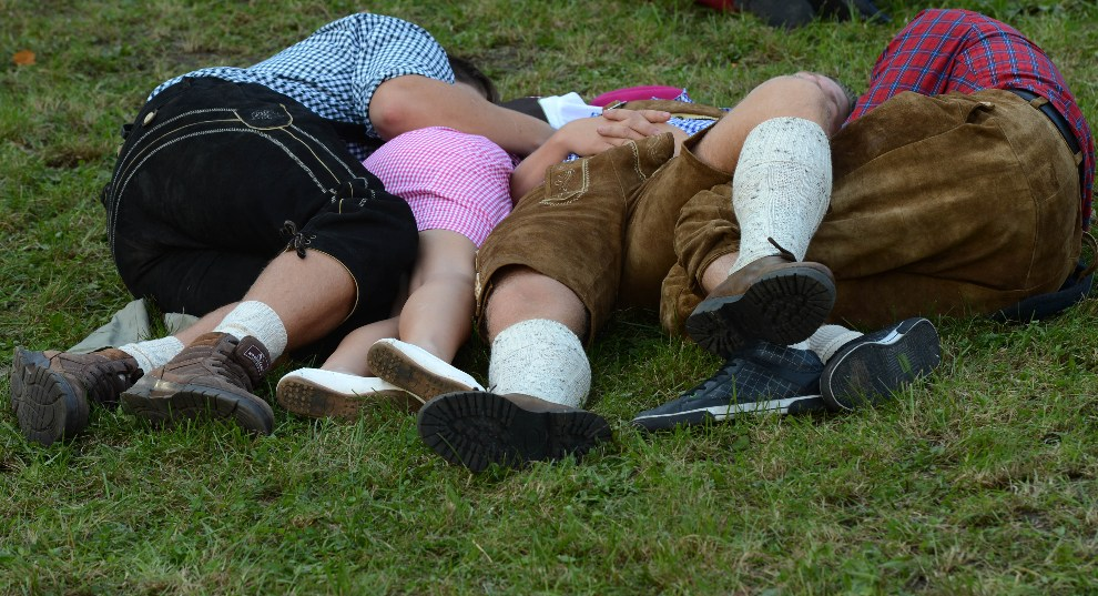 28.NIEMCY, Monachium, 23 września 2012: Uczestnicy zabawy odpoczywają na trawniku. AFP PHOTO / CHRISTOF STACHE