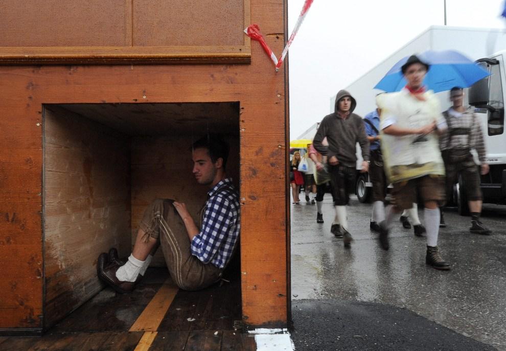 29.NIEMCY, Monachium, 22 września 2012: Mężczyzna kryjący się przed deszczem. EPA/TOBIAS HASE Dostawca: PAP/EPA.