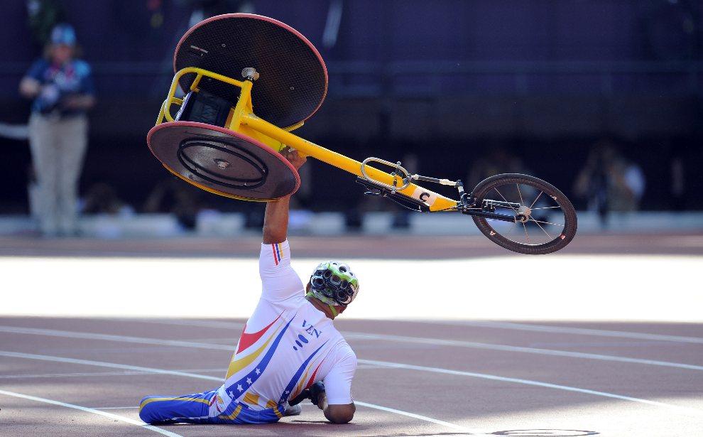 5.WIELKA BRYTANIA, Londyn, 4 września 2012: Jesus Aguilar (Wenezuela) podnosi wózek po tym, jak przewrócił się przed linią końcową wyścigu na 800 m. AFP PHOTO /   GLYN KIRK