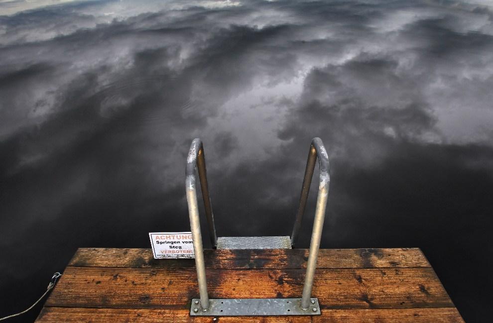 9.NIEMCY, Aitrang, 24 września 2012: Ciemne chmury odbijają się w tafli jeziora Elbsee. AFP PHOTO / KARL-JOSEF HILDENBRAND