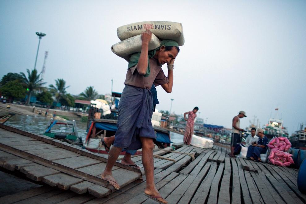 12.MJANMA, Rangun, 9 grudnia 2010: Pracownik portu ładuje cement na pokład łodzi. (Foto:  Drn/Getty Images)