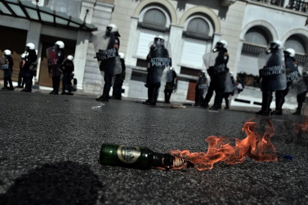 17.GRECJA, Ateny, 18 października 2012: Koktajl Mołotowa palący się przed oddziałem policji. AFP PHOTO / ARIS MESSINIS