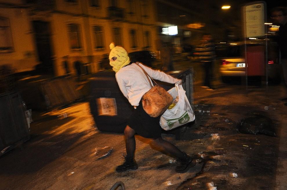 18.PORTUGALIA, Lizbona, 15 października 2012: Demonstrująca kobieta stara się obrzucić śmieciami rezydencję premiera kraju. AFP PHOTO / PATRICIA DE MELO MOREIRA