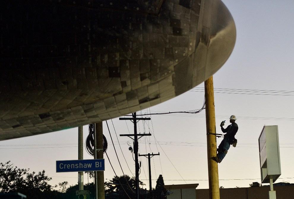 22.USA, Inglewood, 13 października 2012: Mężczyzna wspina się na słup, aby zrobić zdjęcie przejeżdżającemu promowi. (Foto: Jeff Gritchen-Pool/Getty Images)