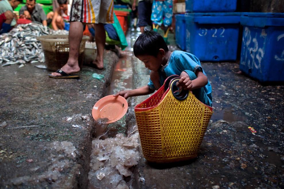 25.MJANMA, Rangun, 9 grudnia 2010: Chłopiec zbiera porozrzucane kawałki lodu. (Foto:  Drn/Getty Images)