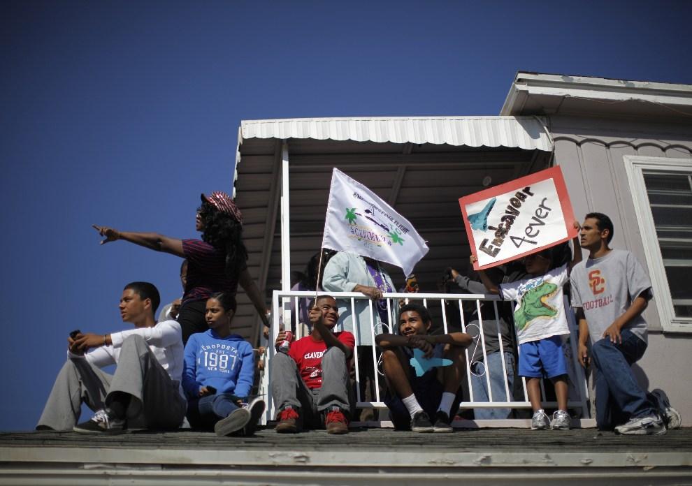 26.1 USA, Inglewood, 13 października 2012: Widzowie obserwują przejazd kolumny z dachu swojego domu. (Foto: Lucy Nicholson-Pool/Getty Images)