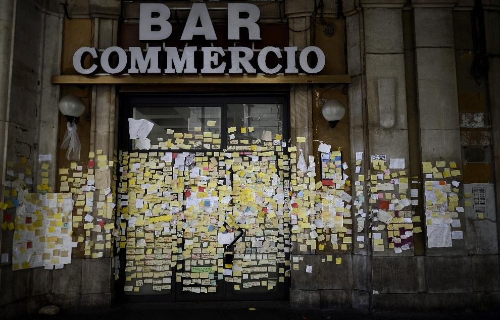 27.WŁOCHY, L'Aquila, 22 października 2012: Karteczki z nazwiskami ofiar trzęsienia ziemi z 2009 roku, przyklejone na drzwiach nieczynnego baru. AFP PHOTO /   FILIPPO MONTEFORTE