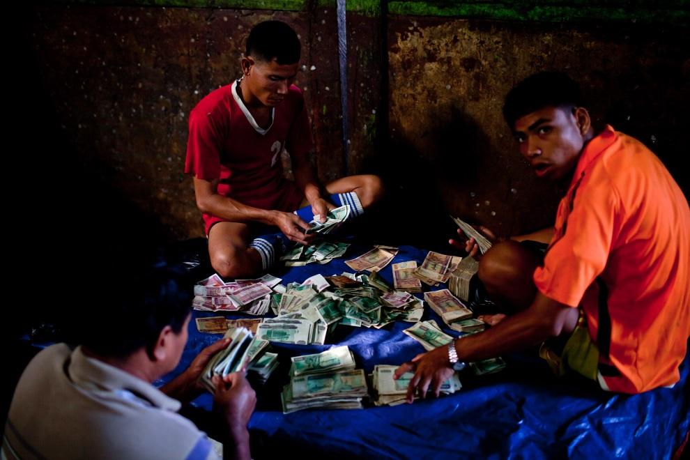 27.MJANMA, Rangun, 9 grudnia 2010: Mężczyźni podliczają pieniądze za sprzedane ryby. (Foto:  Drn/Getty Images)