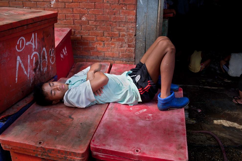 29.MJANMA, Rangun, 9 grudnia 2010: Mężczyzna śpiący na skrzyniach z rybami. (Foto:  Drn/Getty Images)