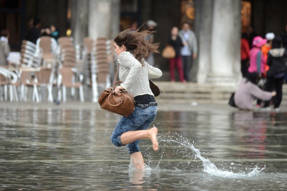 2.WŁOCHY, Wenecja, 15 października 2012: Kobieta biegnie po zalanym wodą Placu Św. Marka. AFP PHOTO / ANDREA PATTARO