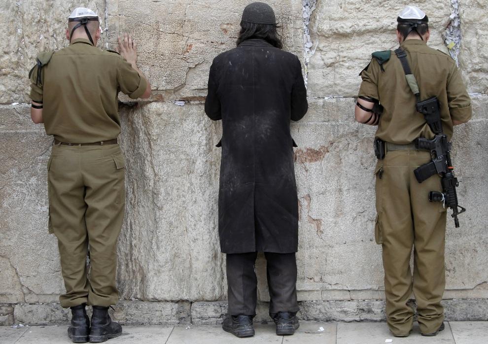 2.IZRAEL, Jerozolima, 22 października 2012: Izraelscy żołnierze i ultraortodoksyjny Żyd modlą się przed Ścianą Płaczu. TOPSHOTS/AFP PHOTO/AHMAD GHARABLI