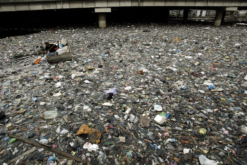 4.INDONEZJA, Surabaya, 17 października 2912: Mężczyzna w łodzi zbiera złom w zanieczyszczonej rzece. AFP PHOTO / JUNI KRISWANTO