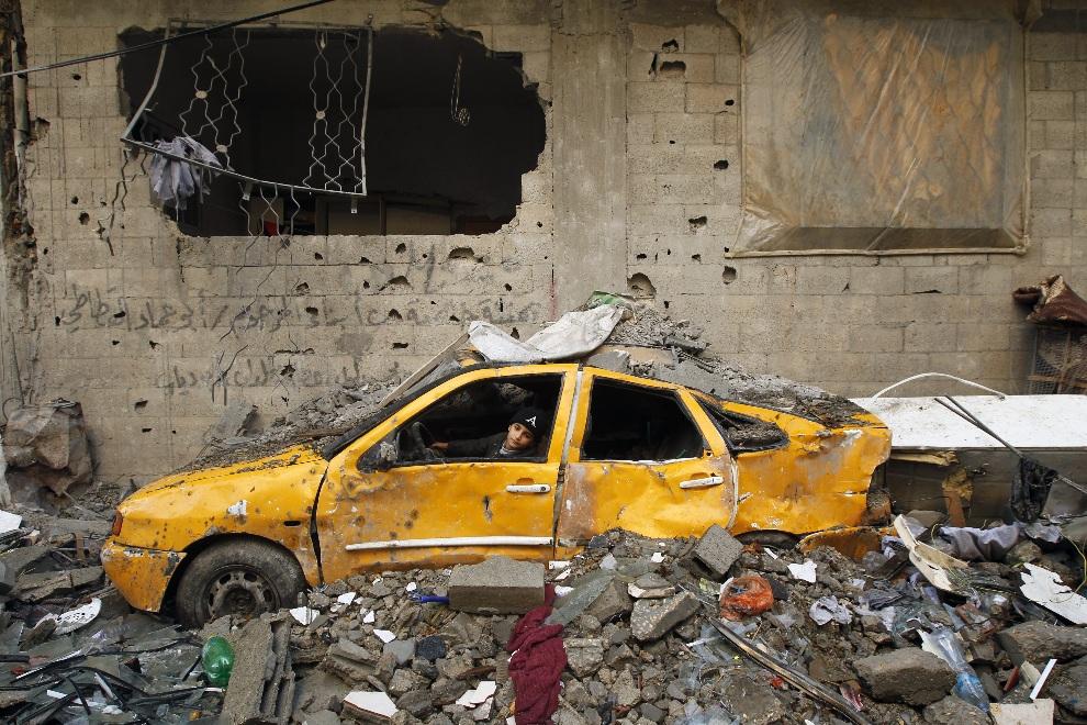 10.STREFA GAZY, 23 listopada 2012: Palestyński chłopiec bawi się w samochodzie zniszczonym podczas nalotu. AFP PHOTO/MOHAMMED ABED