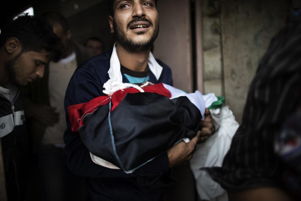 11.STREFA GAZY, 16 listopada 2012: Mężczyzna niesie ciało dziewczynki, która zginęła podczas izraelskiego nalotu. AFP PHOTO/MARCO LONGARI