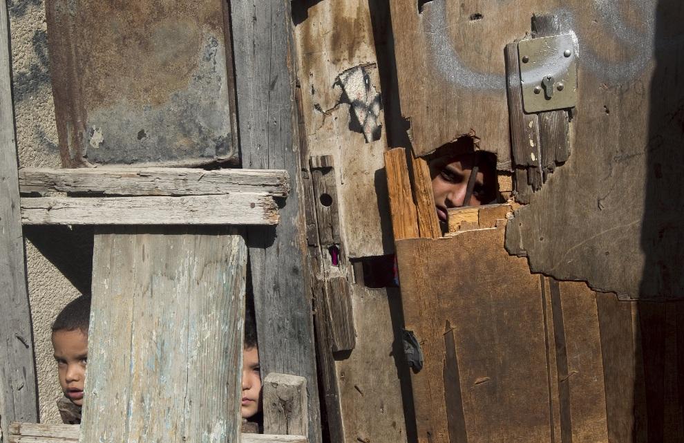 13.STREFA GAZY, 3 listopada 2012: Chłopcy wyglądający przez dziury w drzwiach domu w obozie  Shati. AFP PHOTO/MAHMUD HAMS