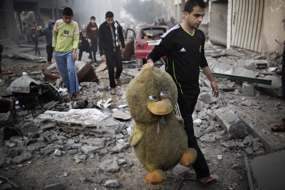 13.STREFA GAZY, 19 listopada 2012: Mężczyzna z pluszową zabawką na zbombardowanej ulicy. AFP PHOTO/MARCO LONGARI