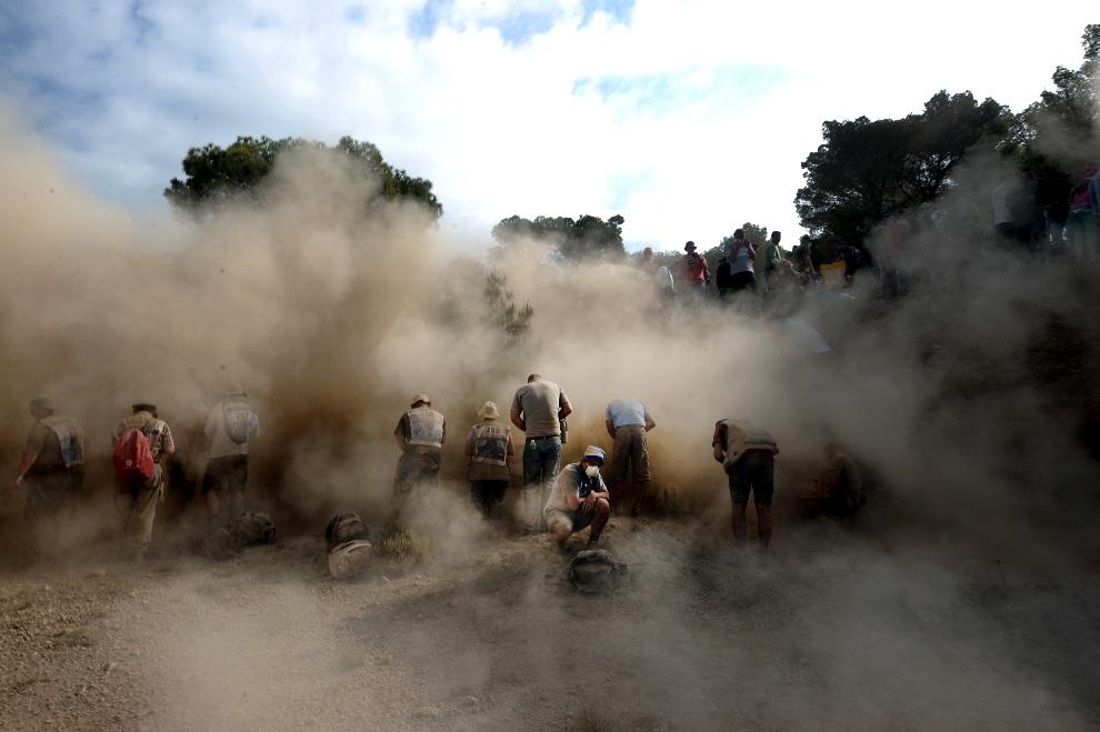 13.GRECJA, Loutraki, 27 maja 2012: Kibice w tumanach kurzu pozostawionych przez przejeżdżający samochód. AFP PHOTO / ARIS MESSINIS