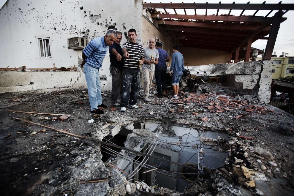 15.IZRAEL, Ofakim, 18 listopada 2012: Mężczyźni przyglądają się stratom wyrządzonym przez eksplozję rakiety. AFP PHOTO/MENAHEM KAHANA