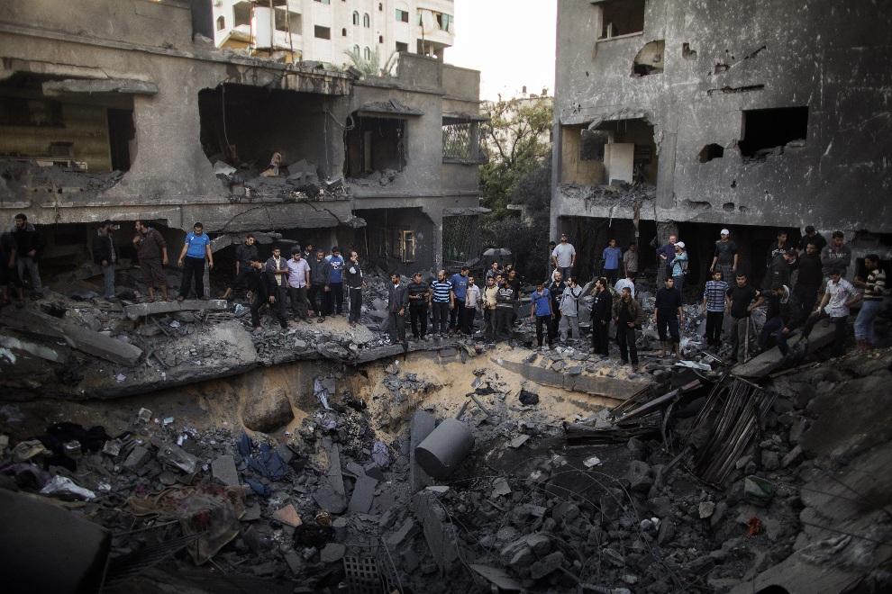 16.STREFA GAZY, 18 listopada 2012: Mężczyźni przyglądają się stratom wyrządzonym przez eksplozję pocisku. AFP PHOTO/MARCO LONGARI