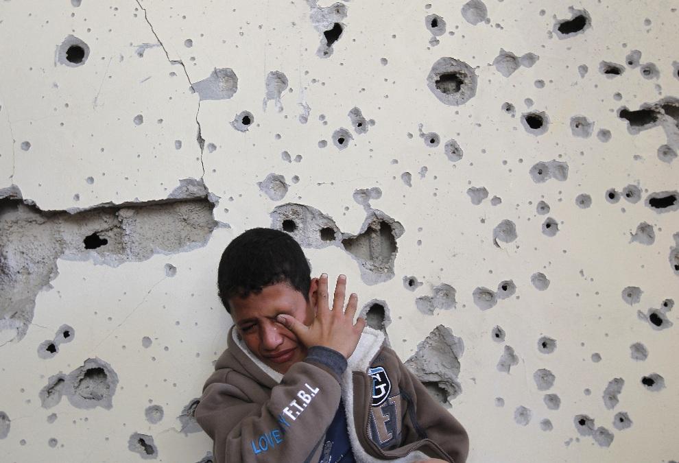 17.STREFA GAZY, 16 listopada 2012: Fares Sadallah (11 lat) przed ostrzelaną ścianą domu rodzinnego. AFP PHOTO/MOHAMMED ABED