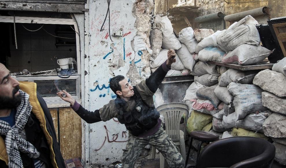 18.SERIA, Aleppo, 6 listopada 2012: Rebeliant rzuca granatem w kierunku pozycji wojsk rządowych. AFP PHOTO/JOHN CANTLIE