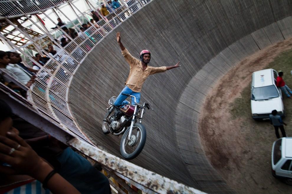 """18.INDIE, Sonepur, 15 listopada 2011: Kaskader w trakcie występu w """"studni śmierci"""". (Foto: Daniel Berehulak/Getty Images)"""