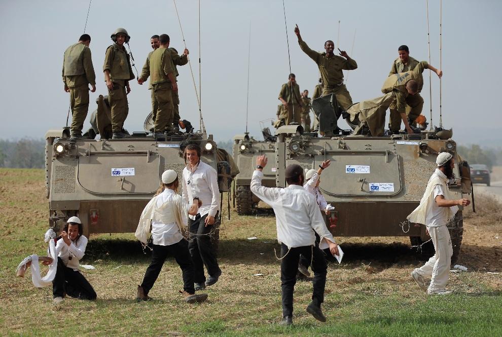 18.STREFA GAZY, 22 listopada 2012: Chasydzcy chłopacy tańczą przed pojazdami wojskowymi. (Foto: Christopher Furlong/Getty Images)