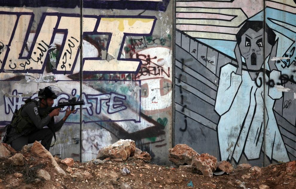 1.ZACHODNI BRZEG, Kalandia, 16 listopada 2012: Izraelski żołnierz mierzy z broni w kierunku protestujących Palestyńczyków. AFP PHOTO / ABBAS MOMANI