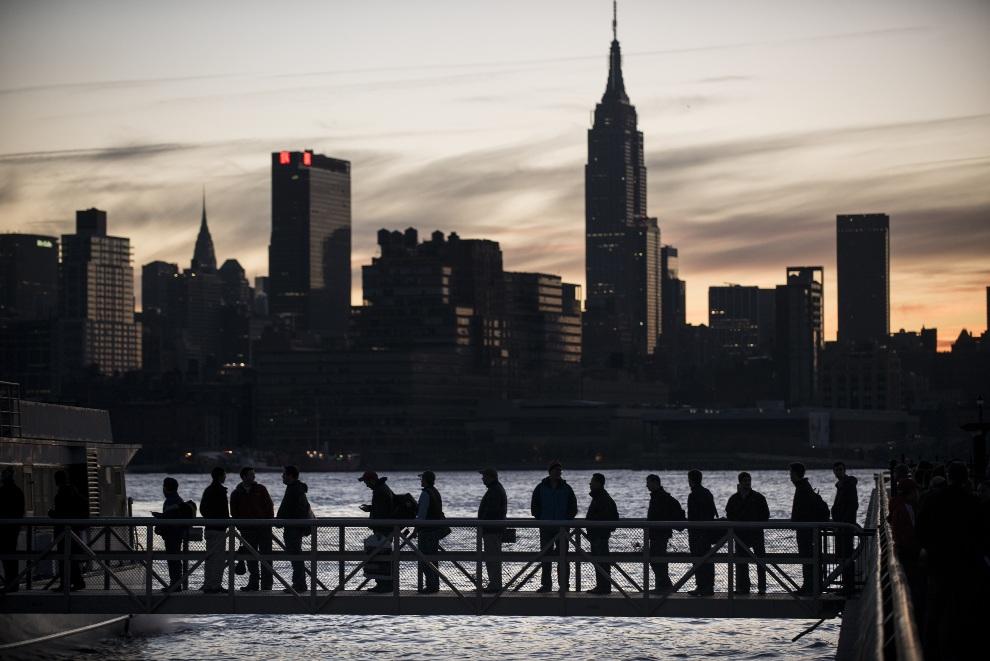 21.USA, Hoboken, 1 listopada 2012: Pasażerowie wchodzący na pokład promu na tle wieżowców Manhattanu. AFP PHOTO/Brendan SMIALOWSKI