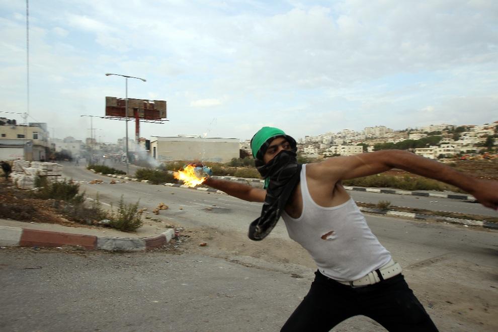 23.ZACHODNI BRZEG, 17 listopada 2012: Student z uniwersytetu w Birzeit podczas starć z izraelskimi żołnierzami. AFP PHOTO/ABBAS MOMANI