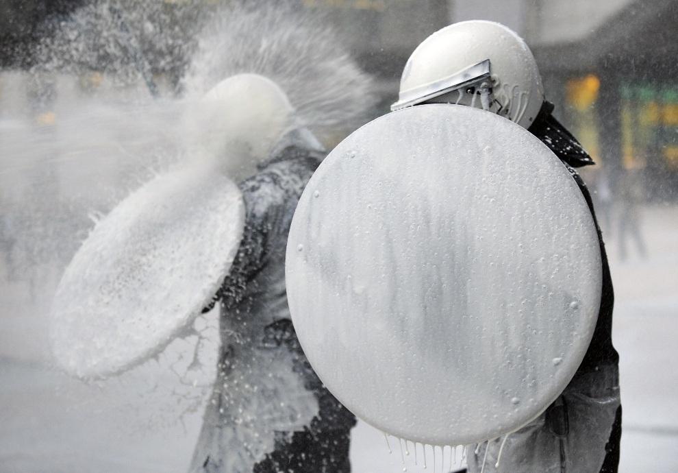 23.BELGIA, Bruksela, 26 listopada 2012: Policjanci polewani mlekiem podczas protest rolników. AFP PHOTO / JOHN THYS
