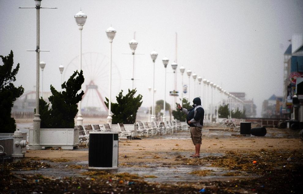 24.USA, Ocean City, 29 października 2012: Mężczyzna fotografujący zniszczenia przy plaży w Ocean City. AFP PHOTO/Jim WATSON