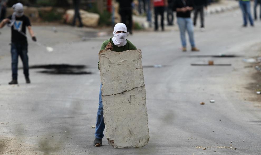 25.ZACHODNI BRZEG, 18 listopada 2012: Palestyńczyk chroni się za prowizoryczną tarczą podczas starć z wojskiem.. AFP PHOTO/ABBAS MOMANI