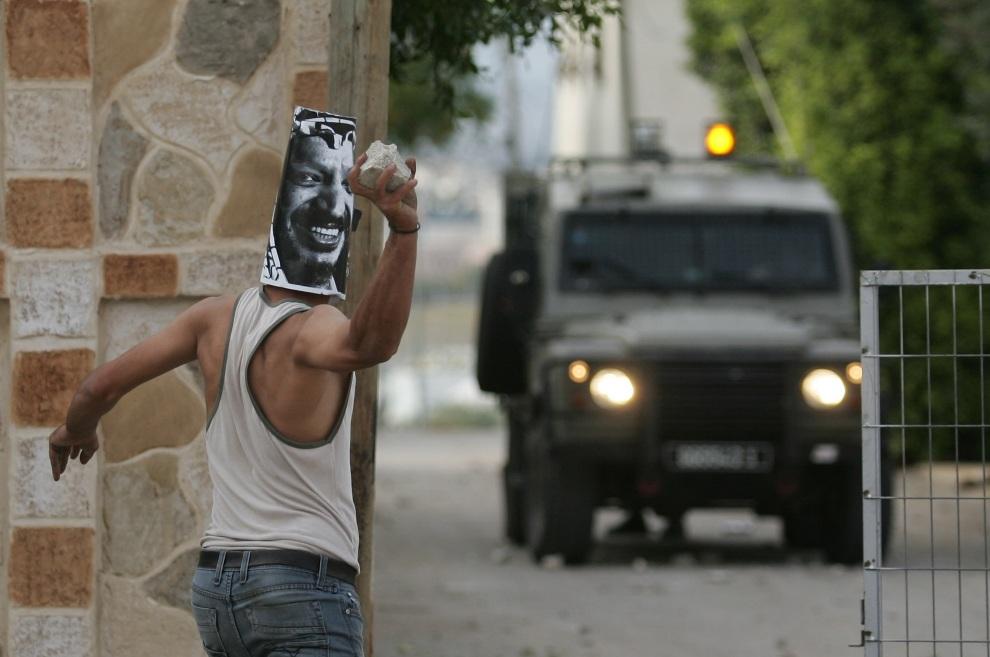 26.ZACHODNI BRZEG, 16 listopada 2012: Palestyńczyk w masce z podobizną  Jasera Arafata atakuje wojskowy patrol. AFP PHOTO / SAIF DAHLAH