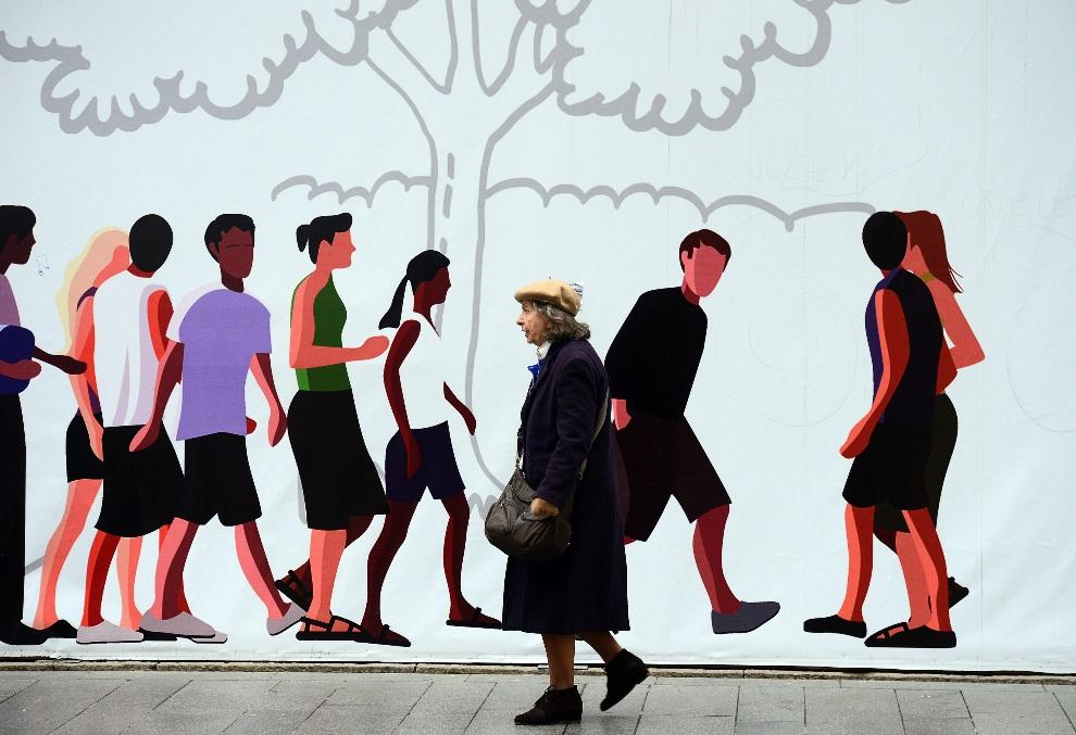 27.WŁOCHY, Mediolan, 29 listopada 2012: Starsza kobieta mija plakat reklamowy w centrum Mediolanu. AFP PHOTO / OLIVIER MORIN