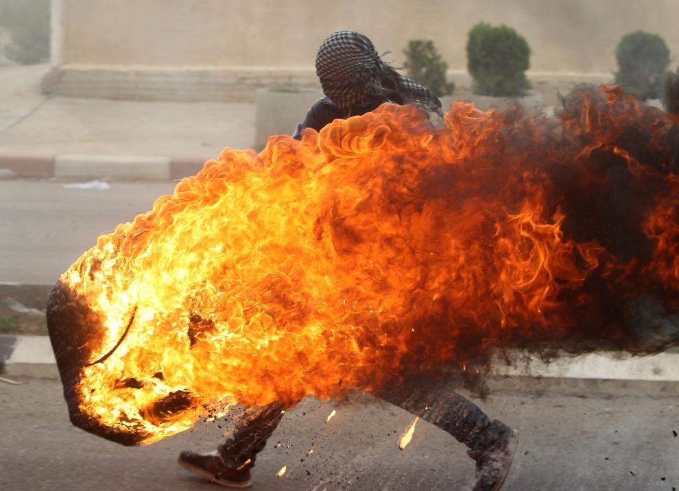 29.ZACHODNI BRZEG, 18 listopada 2012: Palestyńczyk z podpalona oponą podczas walk z żołnierzami. AFP PHOTO/ABBAS MOMANI