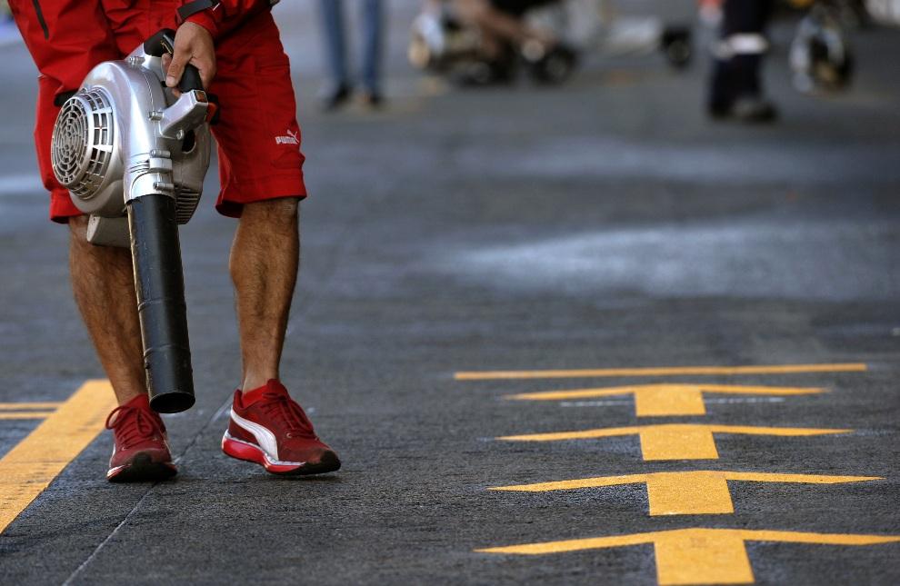 2.BELGIA, Spa, 1 września 2012: Mechanik osusza asfalt w alei serwisowej podczas trzeciej sesji treningowej. AFP PHOTO / THOMAS KIENZLE