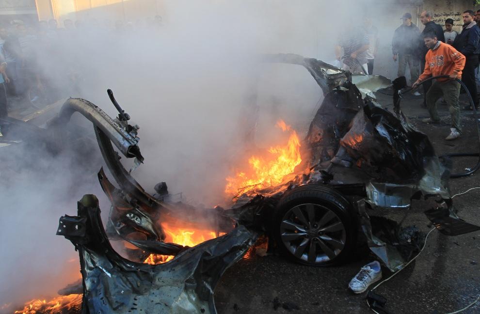 2.STREFA GAZY, 14 listopada 2012: Palestyńscy strażacy gaszą szczątki samochodu, w którym w izraelskim ataku zginął przywódca zbrojnego skrzydła Hamasu, Ahmed   Jaabari. AFP PHOTO/MAHMUD HAMS