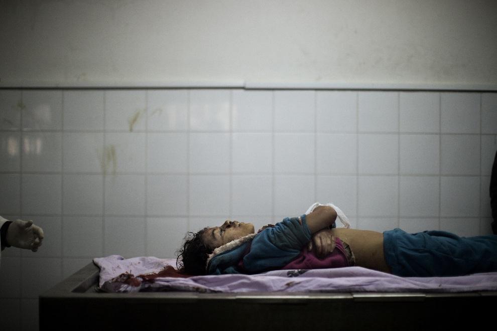 30.STREFA GAZY, 18 listopada 2012: Ciało dziewczynki, ofiary nalotu, złożone w kostnicy. AFP PHOTO/MARCO LONGARI