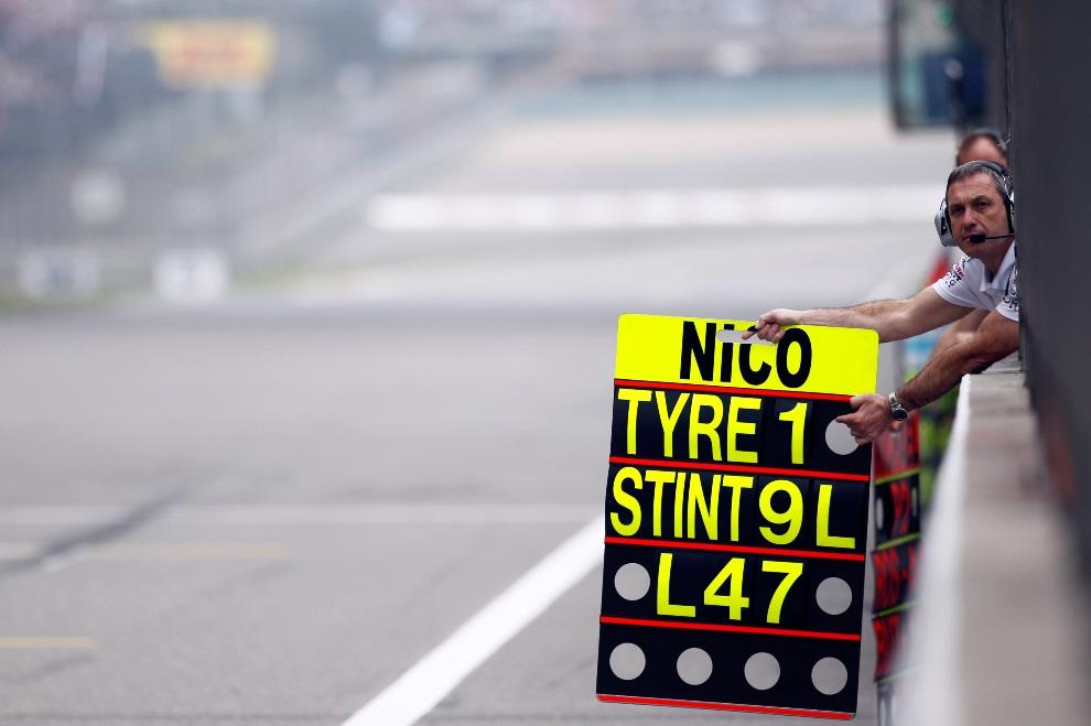 31.CHINY, Szanghaj, 15 kwietnia 2012: Członek zespołu Mercedes przekazuje informacje dla Nico Rosberga. AFP PHOTO / POOL / Aly Song