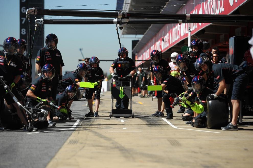 32.HISZPANIA, Montmeló, 11 maja 2012: Mechanicy zespołu ScuderiaToro Rosso przygotowują się do serwisowania samochodu. AFP PHOTO / DIMITAR DILKOFF